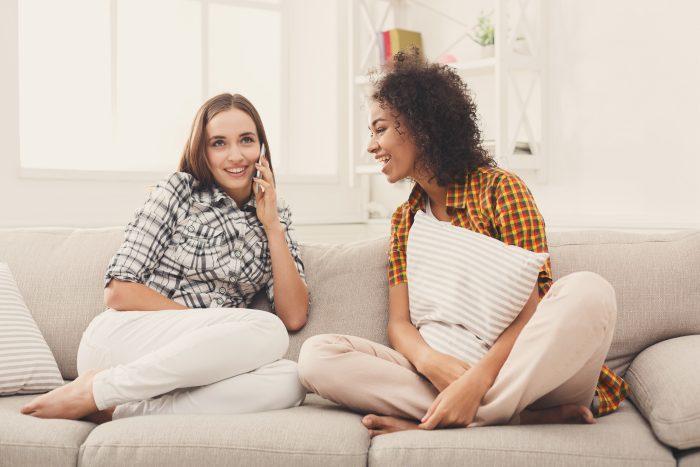 Girl overhearing her friend mobile phone talk