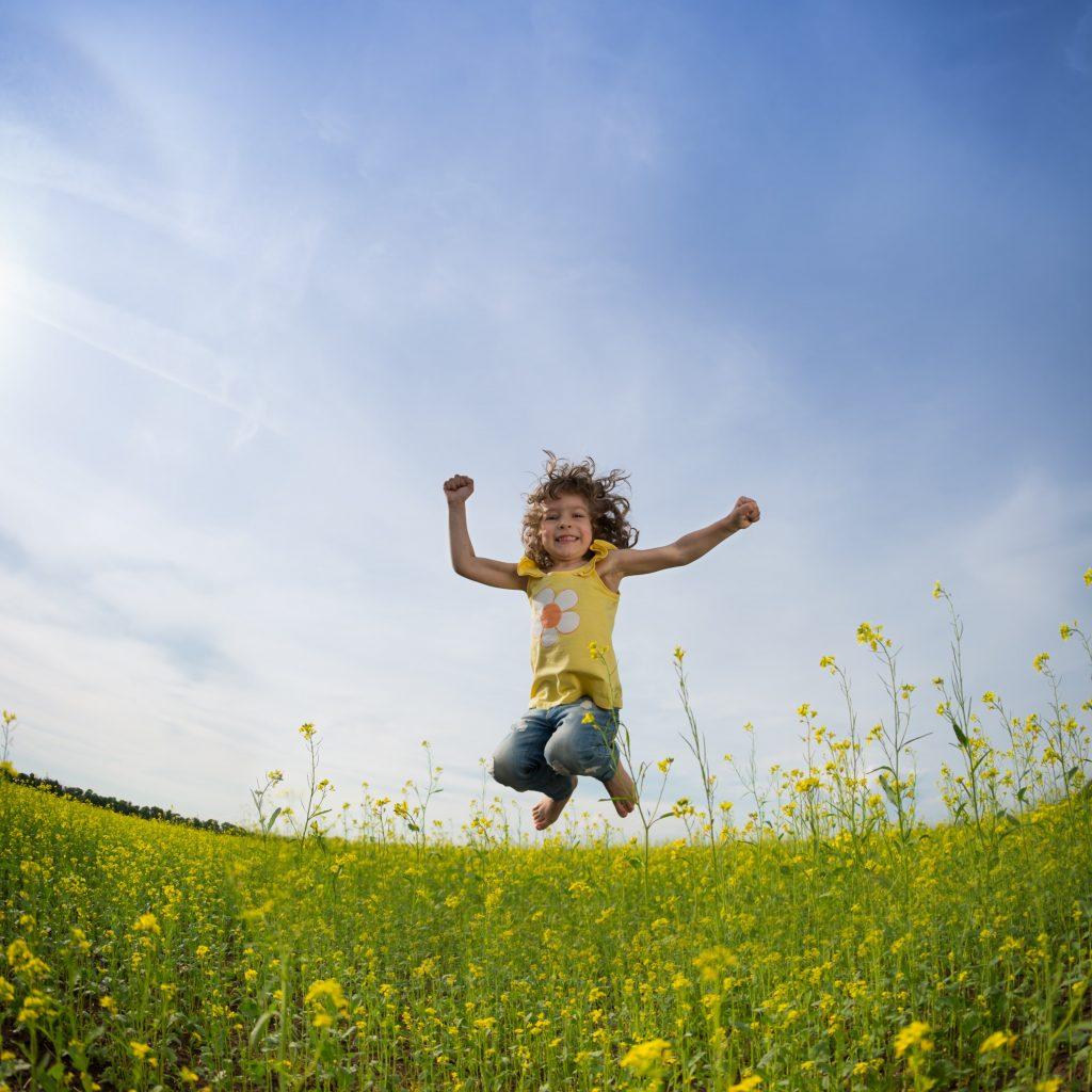 Beautiful little girl jumping for joy