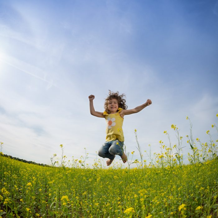 Beautiful little girl jumping for joy